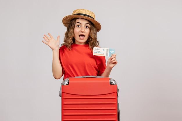 Vista frontal de la chica de vacaciones con valija con billete de viaje