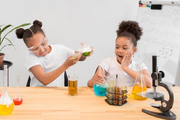 Vista frontal de chicas divirtiéndose con experimentos de química