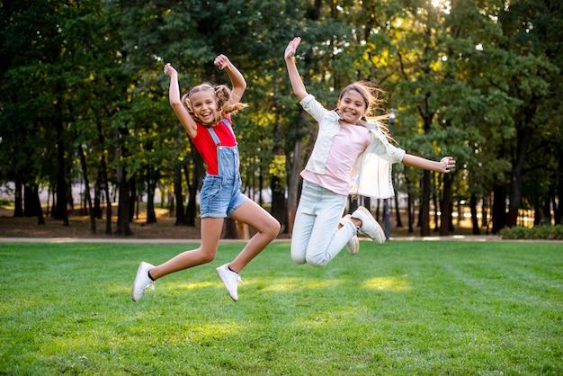 Vista frontal de chicas saltando en el parque