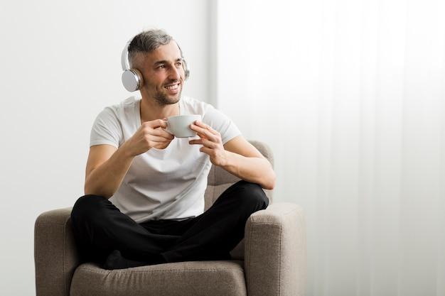 Vista frontal chico con auriculares sosteniendo una taza de café