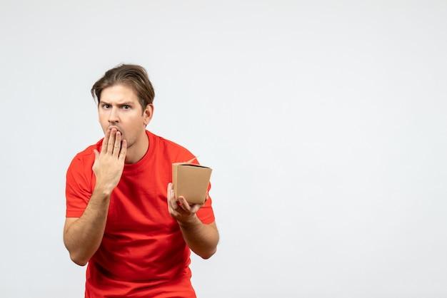 Vista frontal del chico joven en blusa roja sosteniendo una pequeña caja y sintiéndose sorprendido sobre fondo blanco.