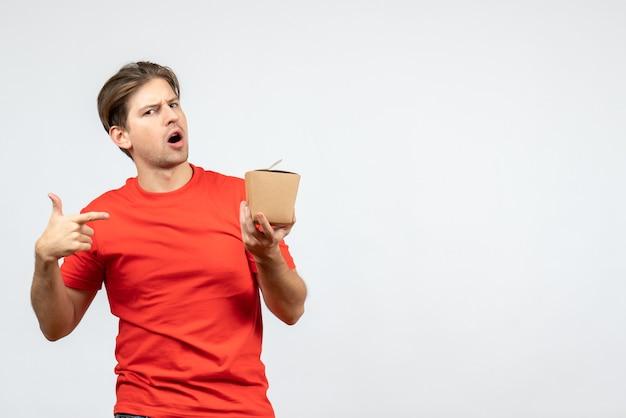 Vista frontal del chico joven confundido en blusa roja apuntando a una pequeña caja sobre fondo blanco.