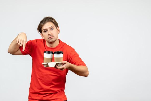 Vista frontal del chico joven confundido en blusa roja sosteniendo café en vasos de papel y apuntando hacia abajo sobre fondo blanco.