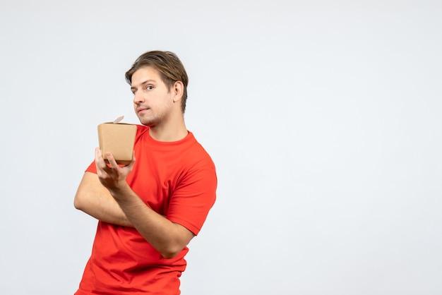 Vista frontal del chico joven confundido en blusa roja sosteniendo una pequeña caja sobre fondo blanco.