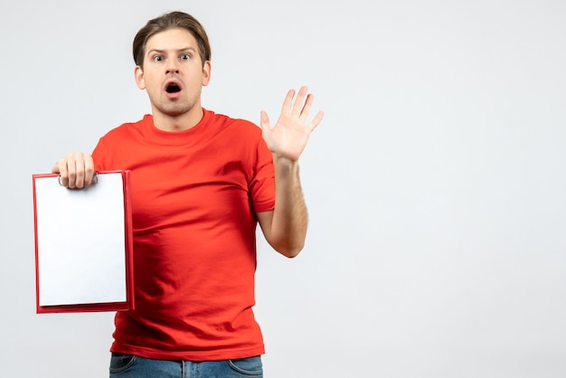 Vista frontal del chico joven emocional confundido en blusa roja con documento que aparece sobre fondo blanco.