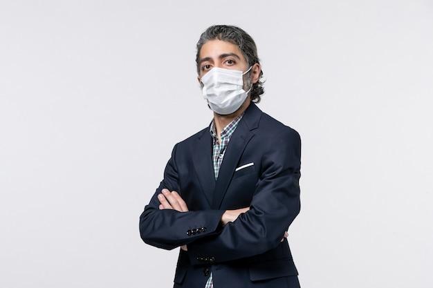 Vista frontal del chico joven serio en traje con máscara sobre superficie blanca