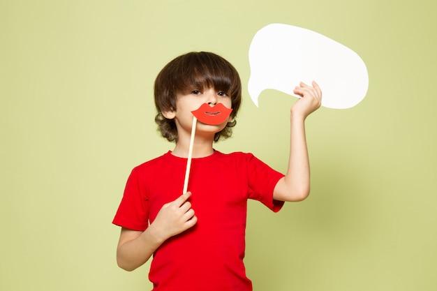 Una vista frontal chico lindo adorable dulce con labios de palo con cartel blanco en el espacio de color piedra