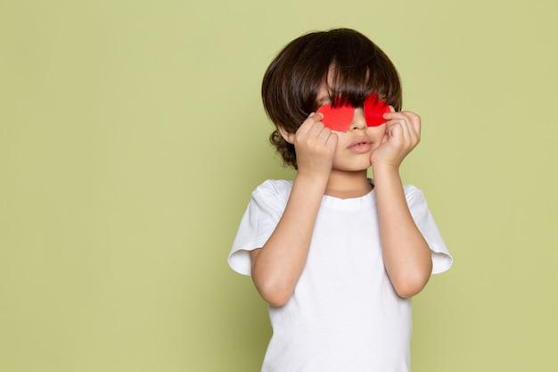 Una vista frontal chico lindo en camiseta blanca con forma de corazón en el espacio de color piedra