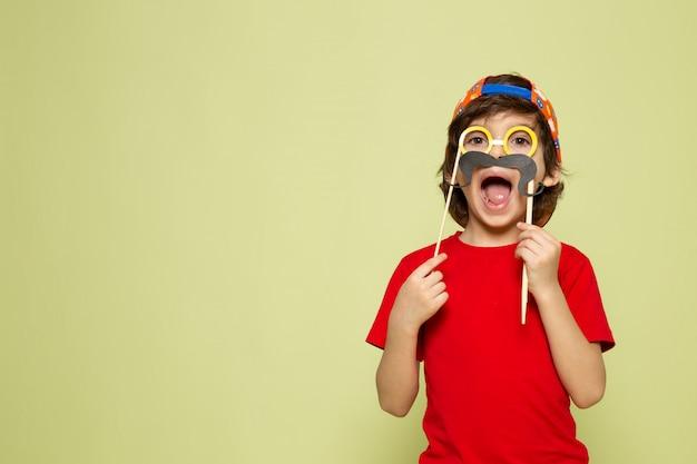 Una vista frontal chico lindo en camiseta roja y gorra de béisbol en el espacio de color piedra
