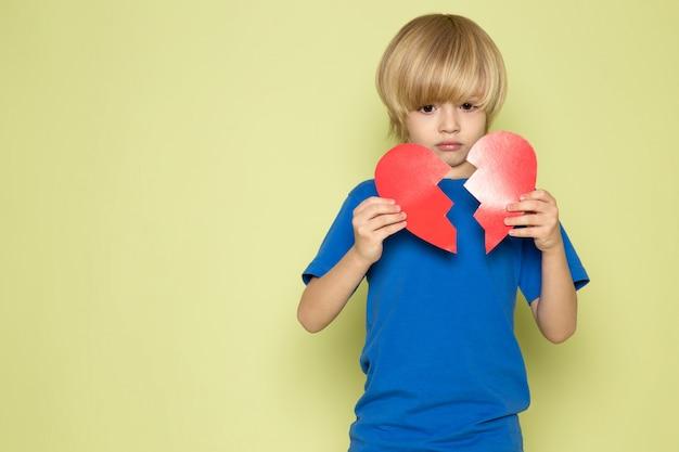 Una vista frontal chico lindo rubio en camiseta azul desgarrando en forma de corazón en el espacio de color piedra