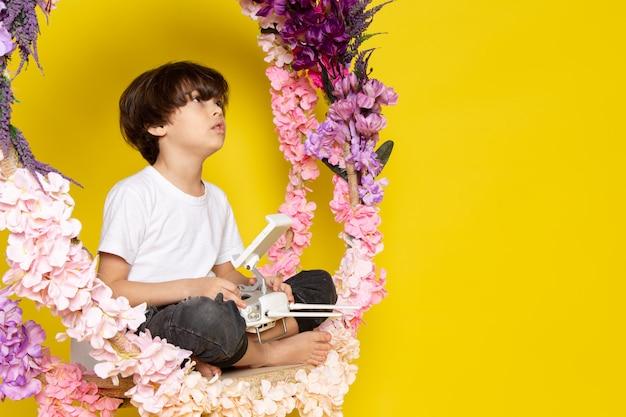 Una vista frontal chico lindo sentado en el puesto de flores en camiseta blanca en el escritorio amarillo
