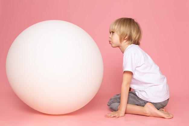 Una vista frontal chico rubio con camiseta blanca junto con una bola blanca sobre el escritorio rosa