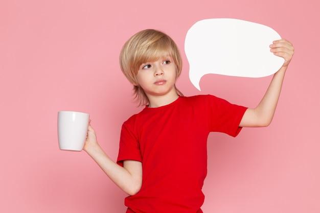 Una vista frontal chico rubio en camiseta roja con cartel blanco y copa en el piso rosa