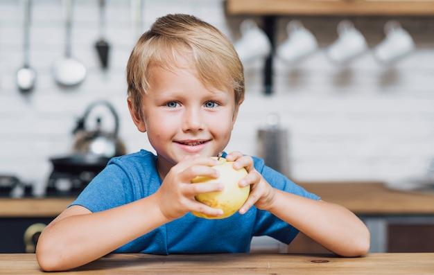 Vista frontal chico rubio comiendo una manzana