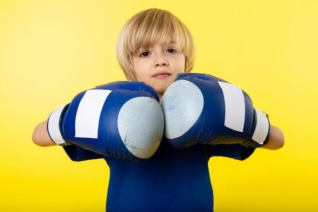 Una vista frontal chico rubio con guantes azules y camiseta azul en la pared amarilla