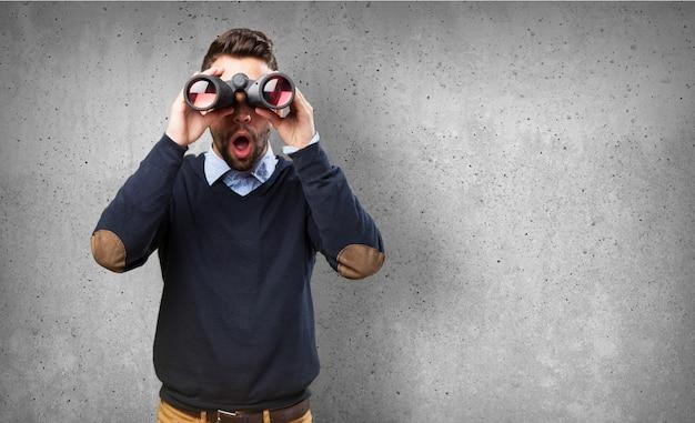 Vista frontal de chico sorprendido con los prismáticos