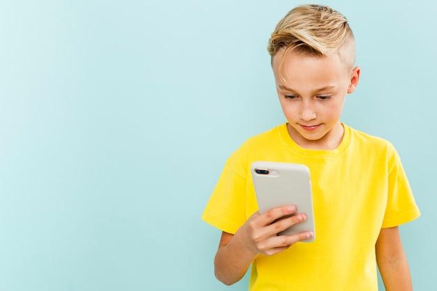 Vista frontal chico usando teléfono con espacio de copia