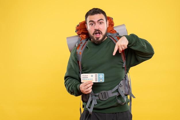 Vista frontal del chico viajero ambicioso emocional con mochila y boleto de retención sobre fondo amarillo