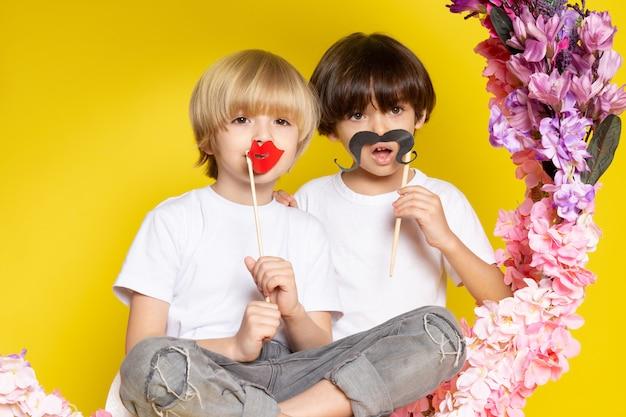 Una vista frontal chicos lindos adorables en camisetas blancas con bigotes en el espacio amarillo
