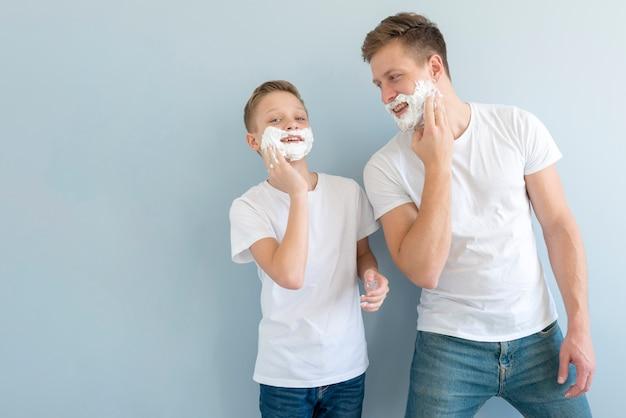 Vista frontal chicos usando espuma de afeitar