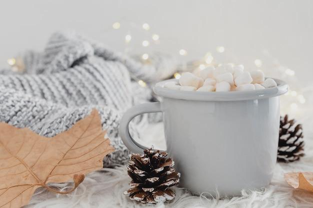 Vista frontal de chocolate caliente con malvaviscos y manta de lana