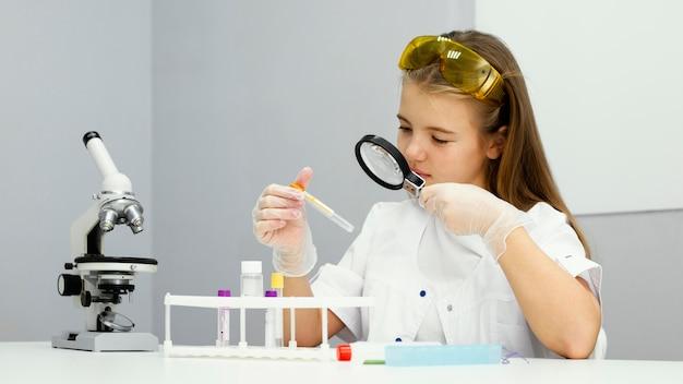 Vista frontal de la científica chica con tubo de ensayo y lupa