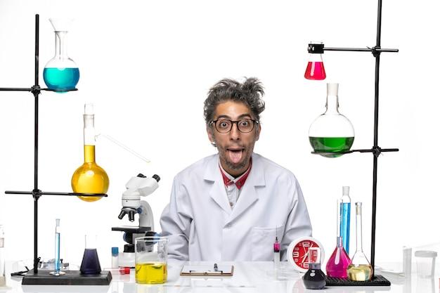Vista frontal científico loco en traje médico posando de manera divertida sobre fondo blanco laboratorio de virus química covid