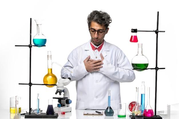 Vista frontal científico masculino en traje médico blanco posando