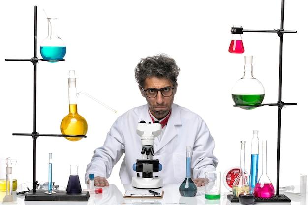 Vista frontal científico masculino en traje médico blanco sentado