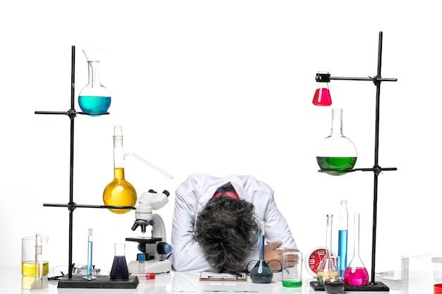 Vista frontal científico masculino en traje médico blanco sintiéndose tan cansado