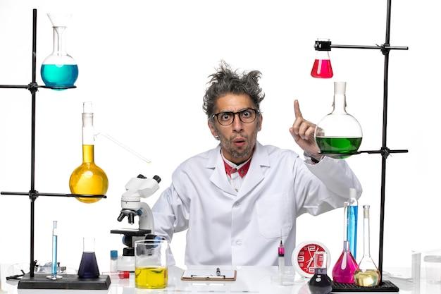 Vista frontal científico masculino en traje médico posando sobre fondo blanco química laboratorio covid virus