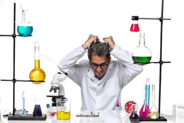 Vista frontal científico masculino en traje médico rasgando su cabello sobre fondo blanco laboratorio de virus química covid