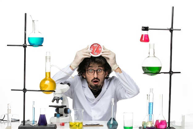 Vista frontal científico masculino en traje médico sosteniendo relojes rojos en el espacio en blanco claro