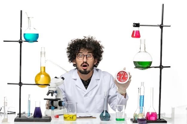 Vista frontal científico masculino en traje médico sosteniendo relojes rojos en el espacio en blanco