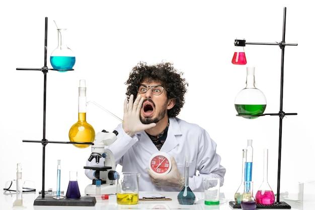 Vista frontal científico masculino en traje médico sosteniendo relojes rojos y gritando en el espacio en blanco