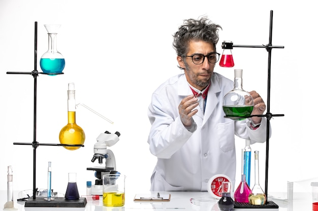 Vista frontal científico masculino en traje médico trabajando con diferentes soluciones en el fondo blanco química covid-virus de laboratorio