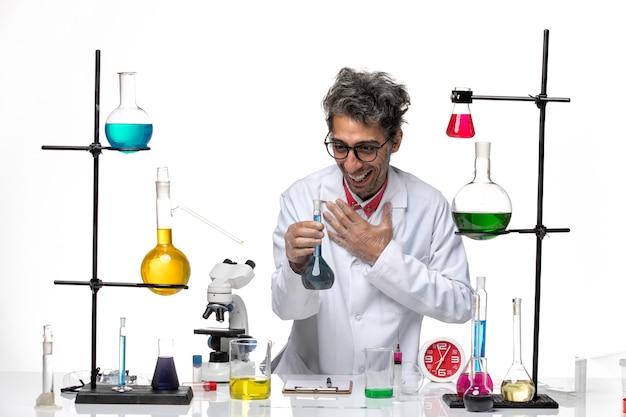 Vista frontal científico masculino en traje médico trabajando con diferentes soluciones y sonriendo sobre fondo blanco coronavirus virus de la salud del laboratorio