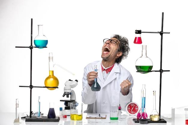 Vista frontal científico masculino en traje médico trabajando con soluciones regocijándose