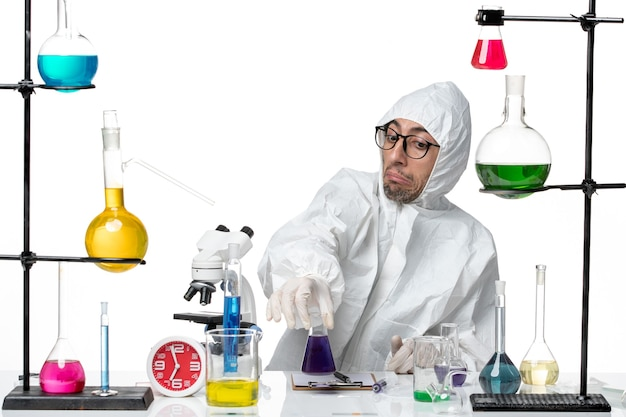 Vista frontal científico masculino en traje de protección especial con matraz con solución púrpura