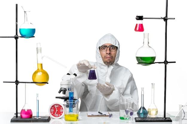 Vista frontal científico masculino en traje de protección especial con matraz con solución