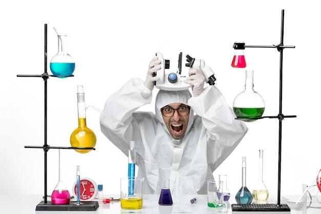 Vista frontal científico masculino en traje de protección especial con microscopio