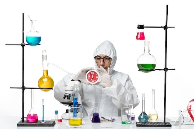 Vista frontal científico masculino en traje de protección especial sosteniendo relojes
