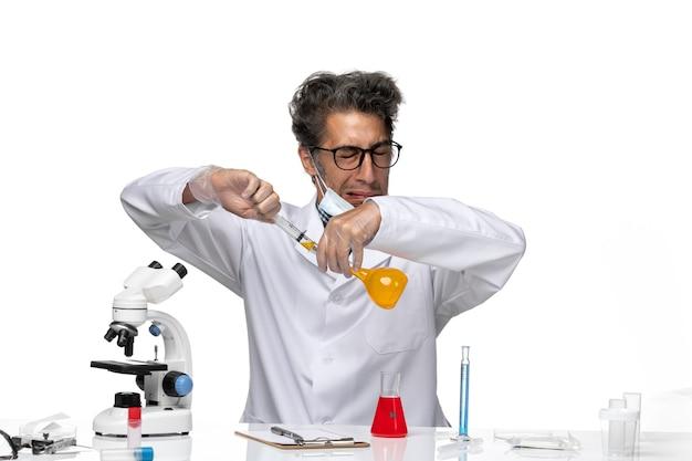 Vista frontal científico de mediana edad en traje médico blanco inyección de llenado