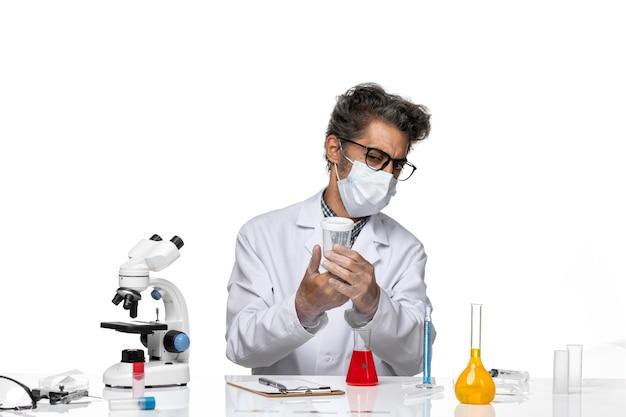 Vista frontal científico de mediana edad en traje médico blanco con matraz