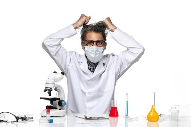 Vista frontal científico de mediana edad en traje médico blanco rasgando su cabello