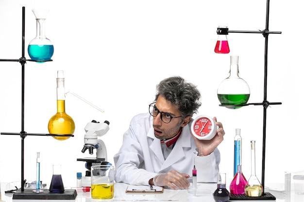 Vista frontal científico de mediana edad en traje médico blanco con reloj
