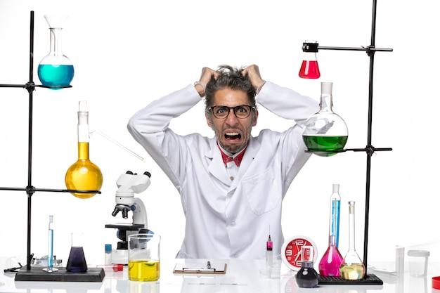 Vista frontal científico de mediana edad en traje médico sentado y rasgando su cabello