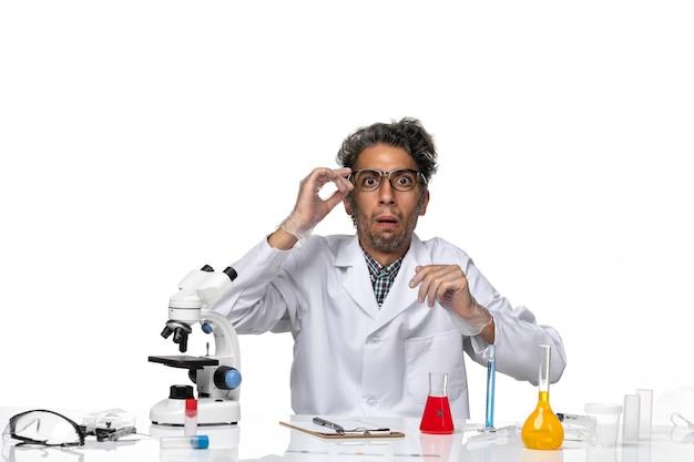 Vista frontal científico de mediana edad en traje médico sentado