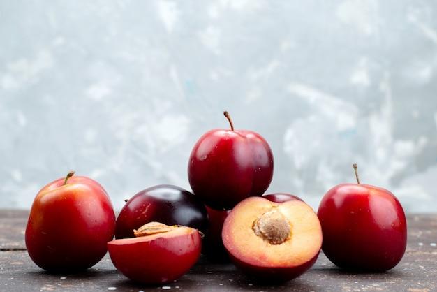 Vista frontal ciruelas agrias frescas jugosas y suaves en madera oscura, árbol frutal de verano frutal