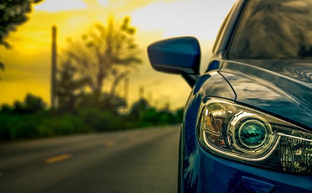 Vista frontal del coche azul suv de lujo estacionado en la carretera de asfalto al atardecer